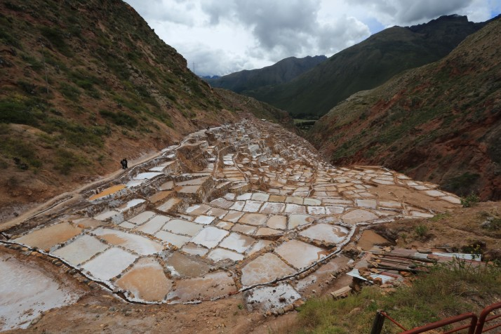 Salt water flows out of the mountain into a system of canals that are fed to pools where the water is evaporated.  First used by the Incas.