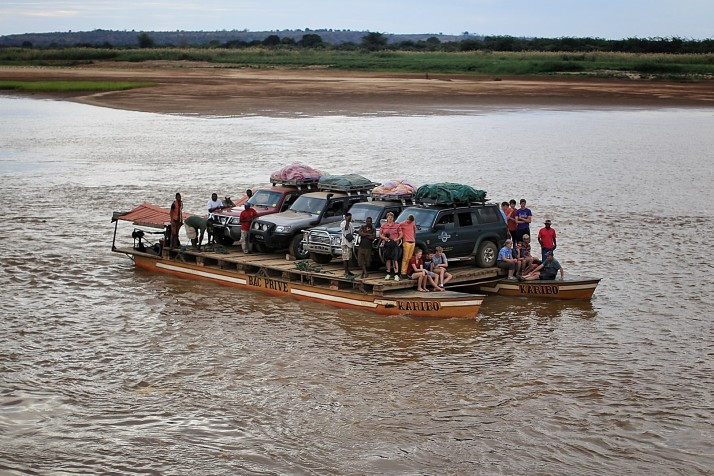 The tourist SUV's on this ferry are riding the same boat which takes supplies to a million people.