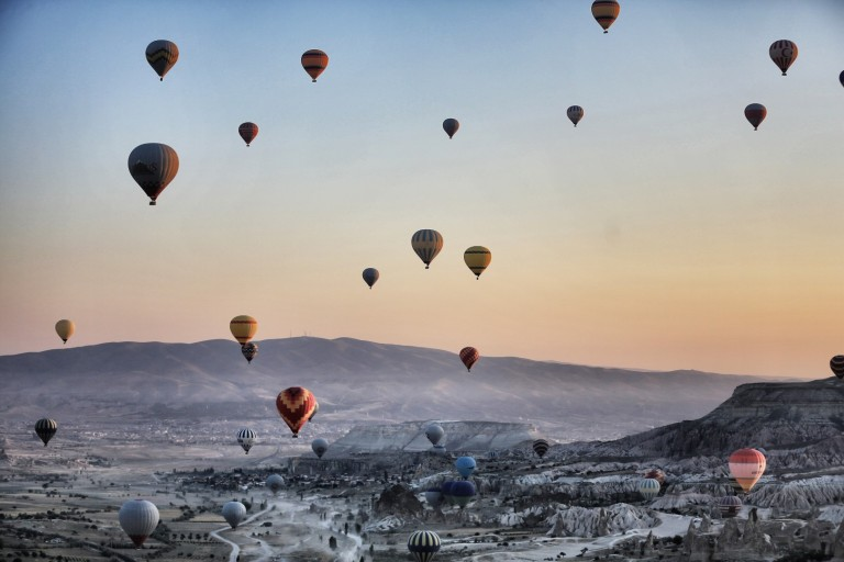 The stunning effect of dozens of balloons launching over a magic landscape