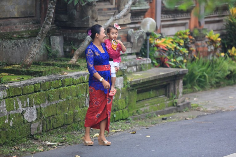 Carrying a child, dressed for the holiday